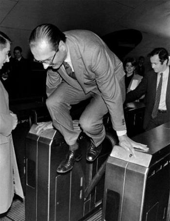 Jacques Chiract pas encore président mais maire de Paris enjambe un tourniquet dans le métro parisien, à la manière d'un resquilleur.  Jean-Claude Delmas, photographe pour l'Agence France-Presse (AFP), est présent. C'est lui qui signe ce cliché .